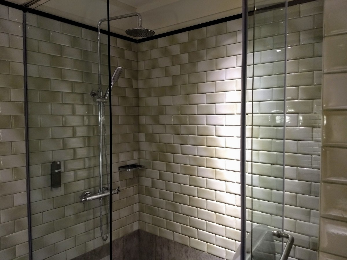 Shower stall to the right with a rain showerhead and hand-held shower.