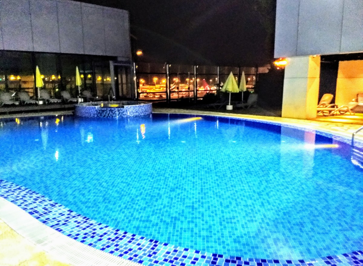 The only transit hotel in Asia with an outdoor swimming pool. Note the lights of the tarmac between the two buildings.