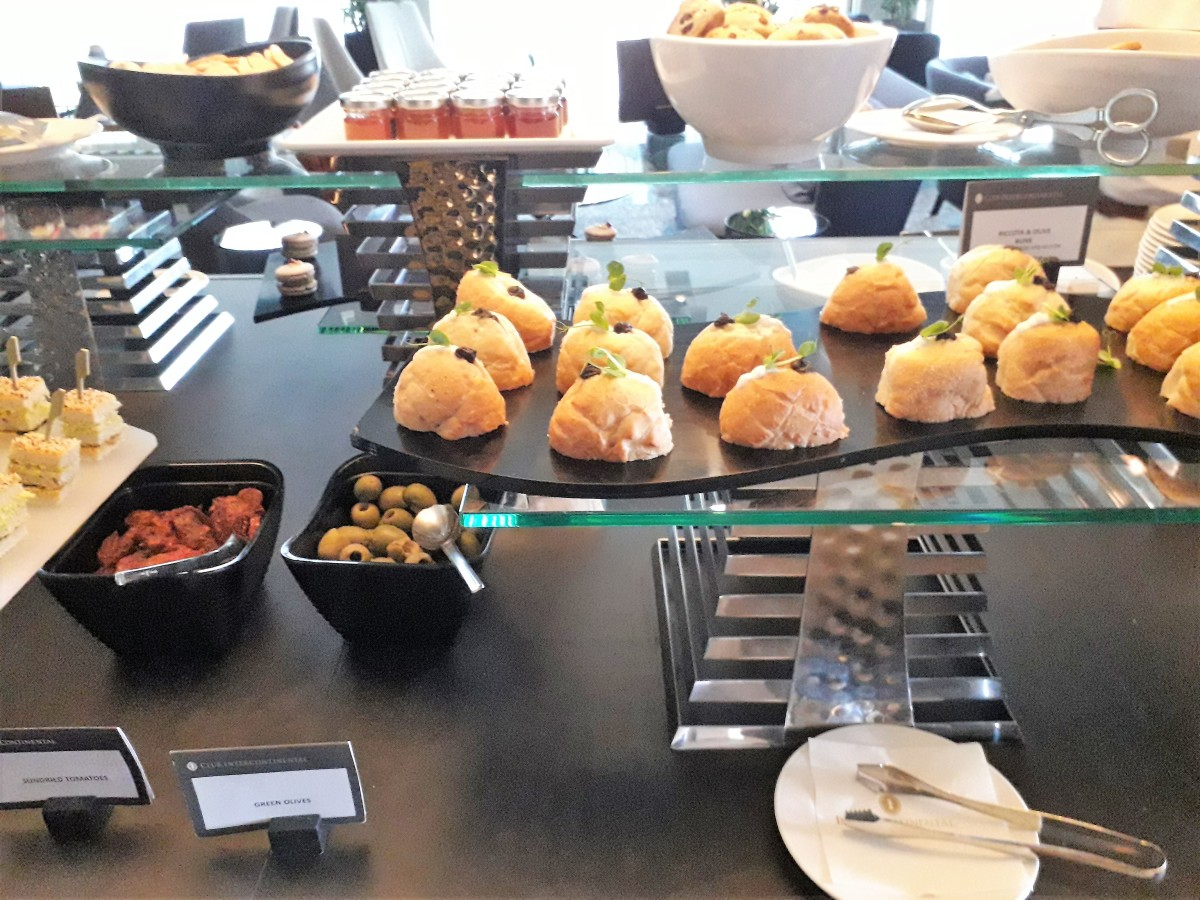 Savory filled buns and accompaniments, with scones and jam behind.