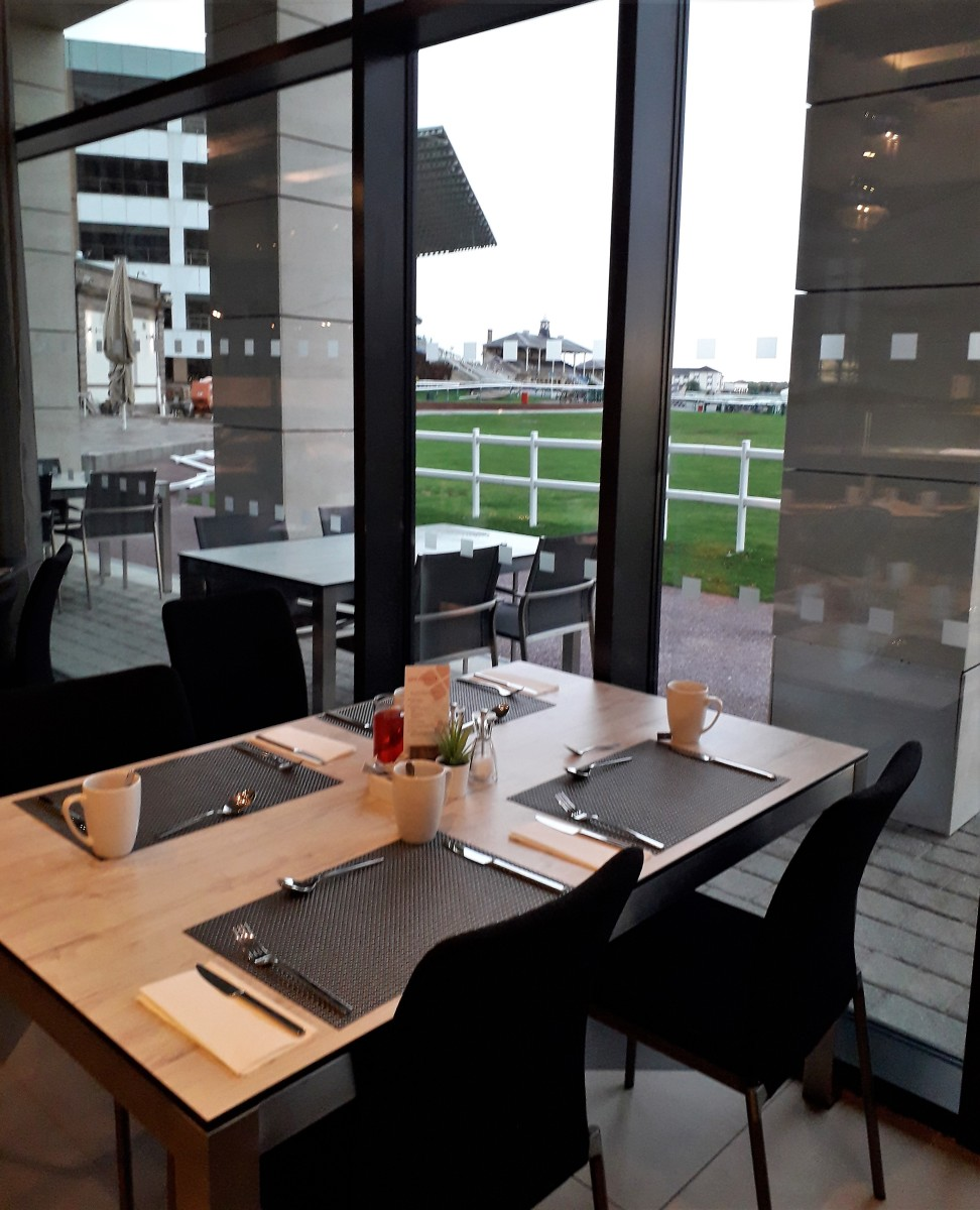 The table is set for breakfast with a racecourse view.