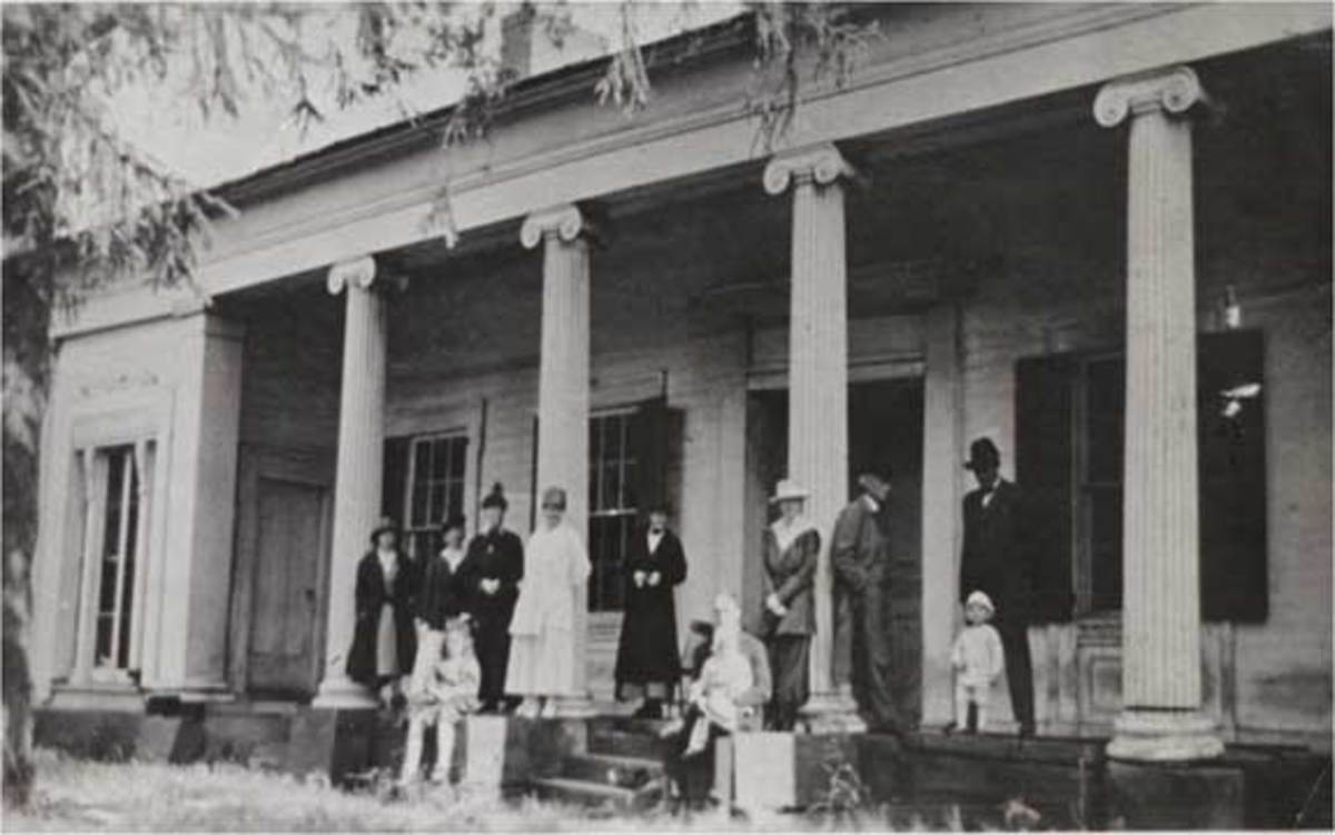 A family picture of the front porch of Swift's Mansion on Gore Orphanage road. There is no information on who the people were, or when this photo was taken.