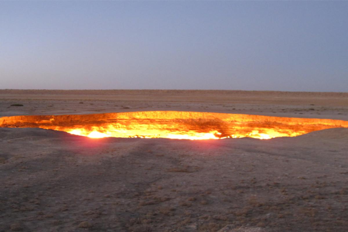 A fiery doorway to Hell that burns amid a barren desert landscape.