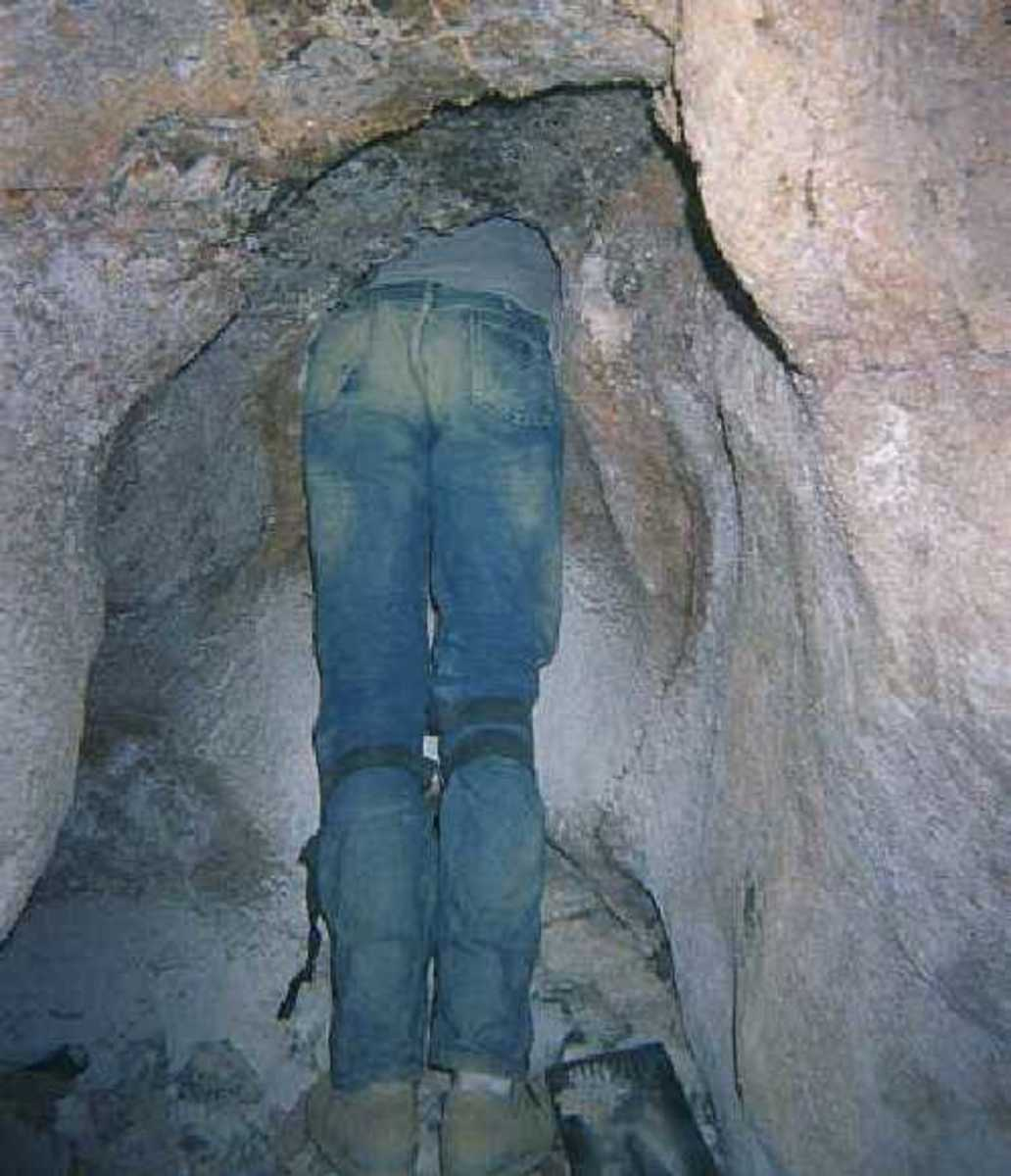 Ted the Caver, fitting himself into the hole that he and a friend opened up to explore an unknown cave.