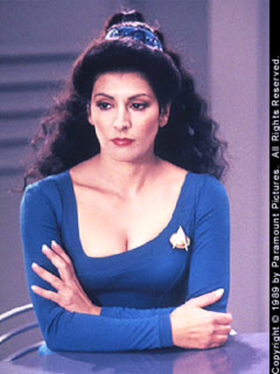 Councillor Deanna Troi, looking very blue in an uneven bra, wishing there was a hairdresser onboard
