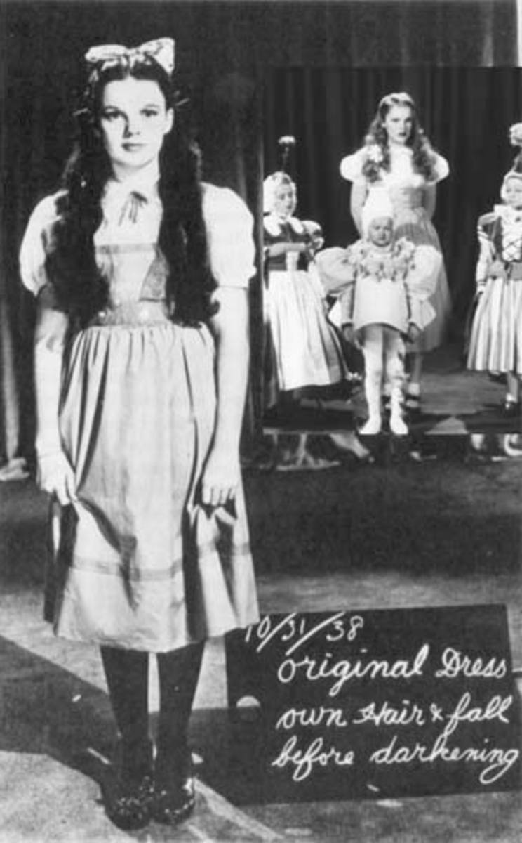 """""""Inset: Judy Garland, wearing a blonde wig and heavy makeup, stands with Munchkins for a color test during Thorpe's reign as director. At left: as she appeared after Cukor's three days on the picture."""""""