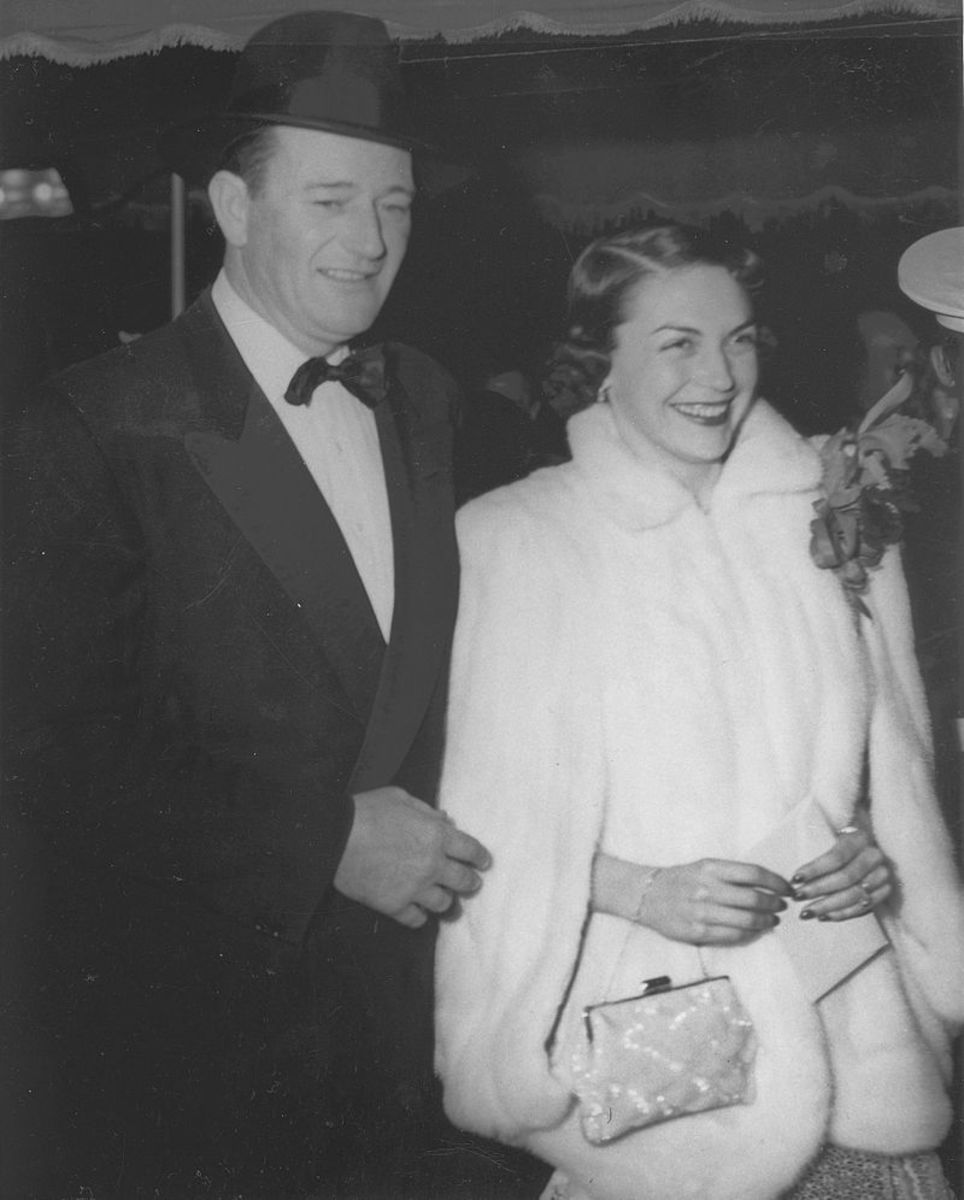 John Wayne and his wife, Esperanza Baur arrive at the Sands of Iwo Jima premiere.