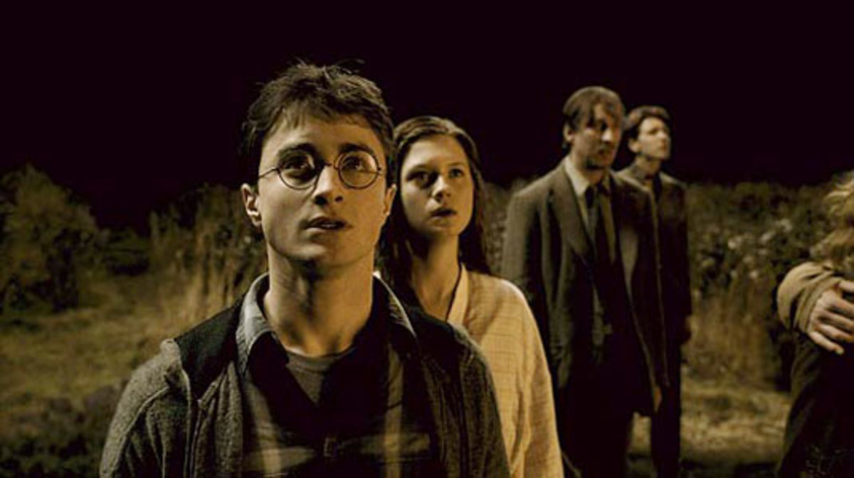 Harry, Ginny, and Lupin watch helplessly as the Weasley home is burned down