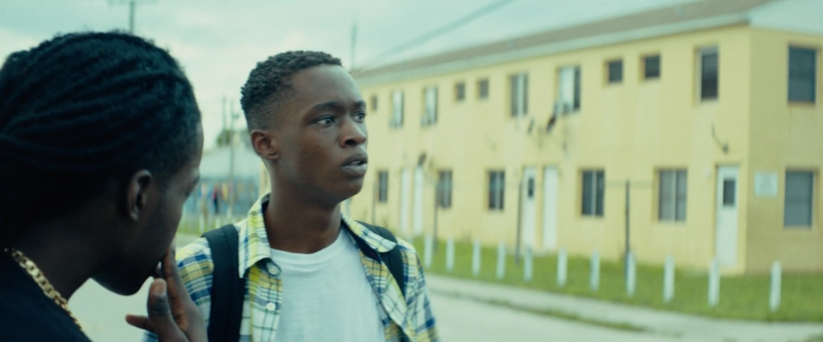 Terrel confronts Chiron by a yellow building.