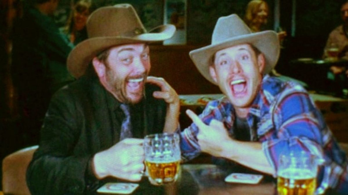 Crowley and Dean kicking back and wearing hats