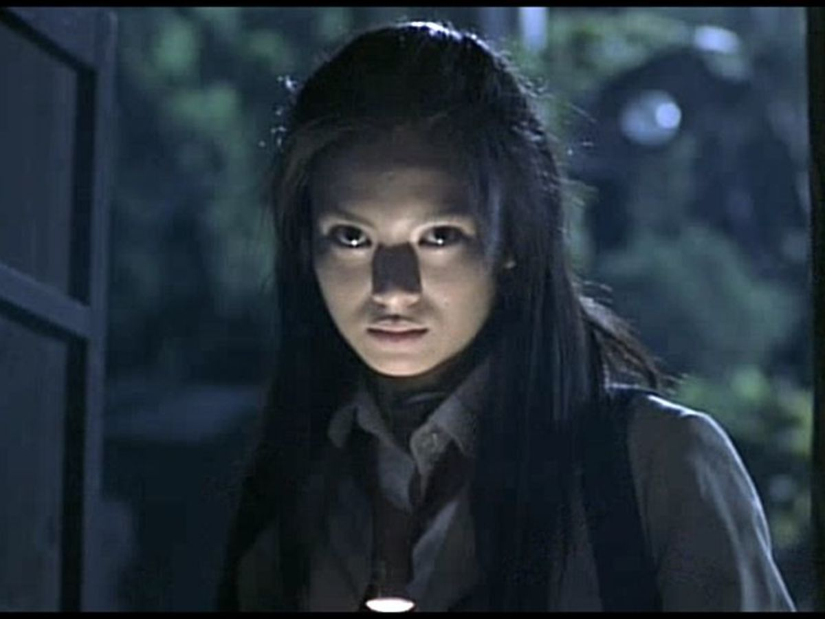 Chiaroscuro lighting from flashlight to demonize Mitsuko. Unintentionally similar to Warwick Davis's Leprechaun.