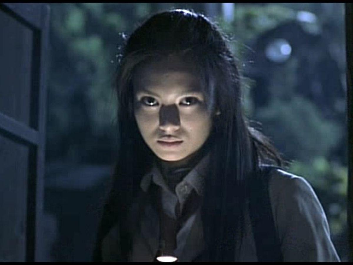 Chiaroscuro lighting from flashlight to demonize Mitsuko. Unintentionally similar to Warwick Davis's Leprechaun.