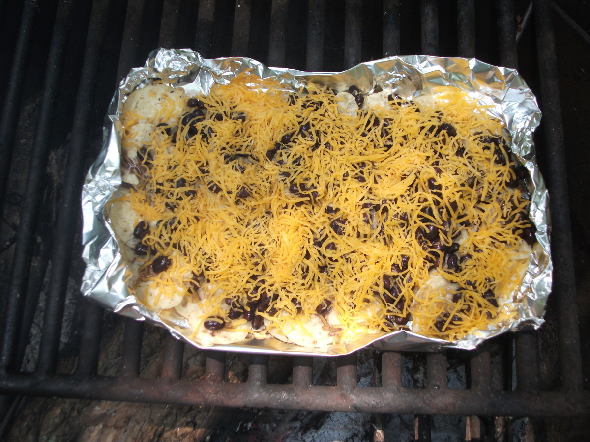 Nachos with chips, black beans, and cheese cooked over a campfire.