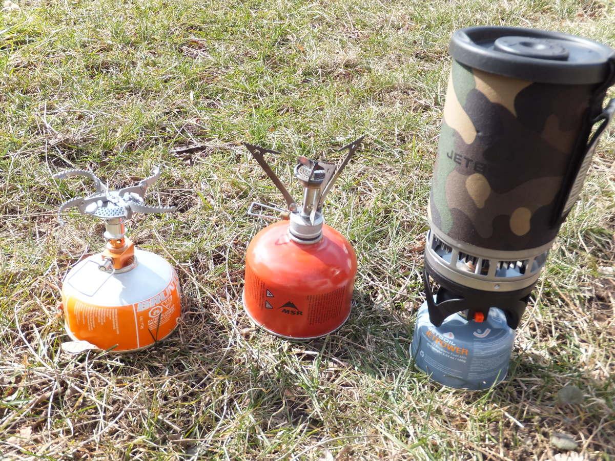 Three iso-butane stoves: Brunton Flex, MSR PocketRocket, and Jetboil PCS.