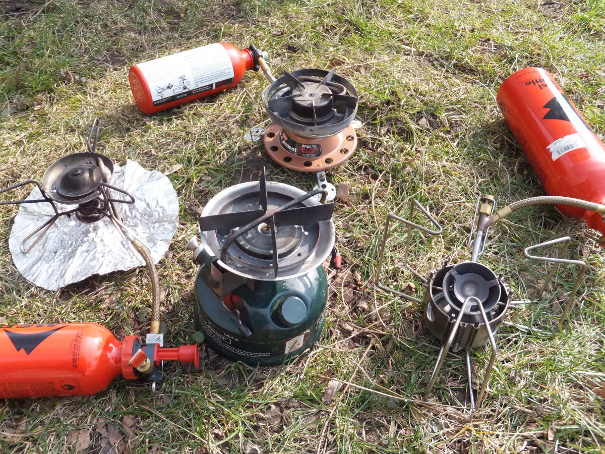 Four white gas stoves: MSR Whisperlite (international), Coleman Peak 1, Coleman Exponent Apex II, and MSR Dragonfly.