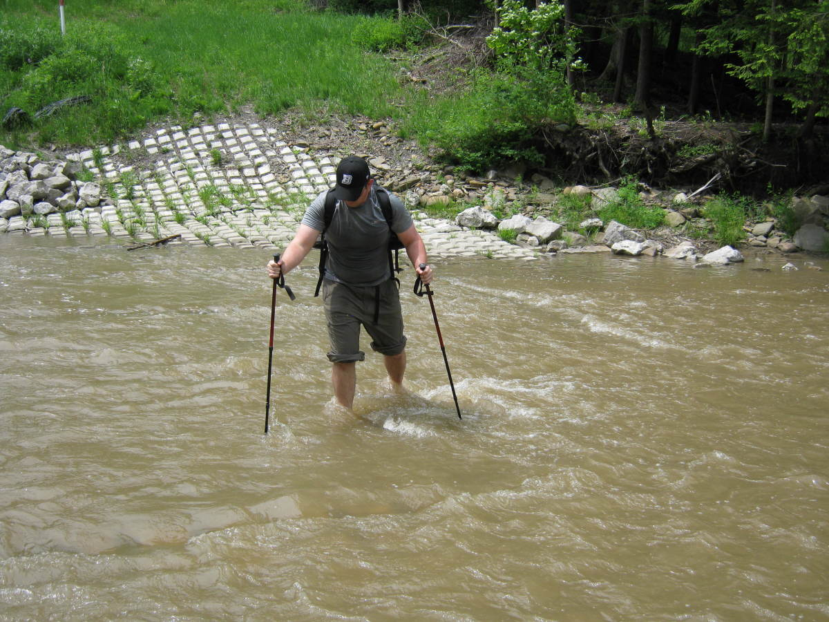 Use trekking poles to reduce stress on knees and stabilize yourself in rough terrain.  They are also great for stream crossings like this.