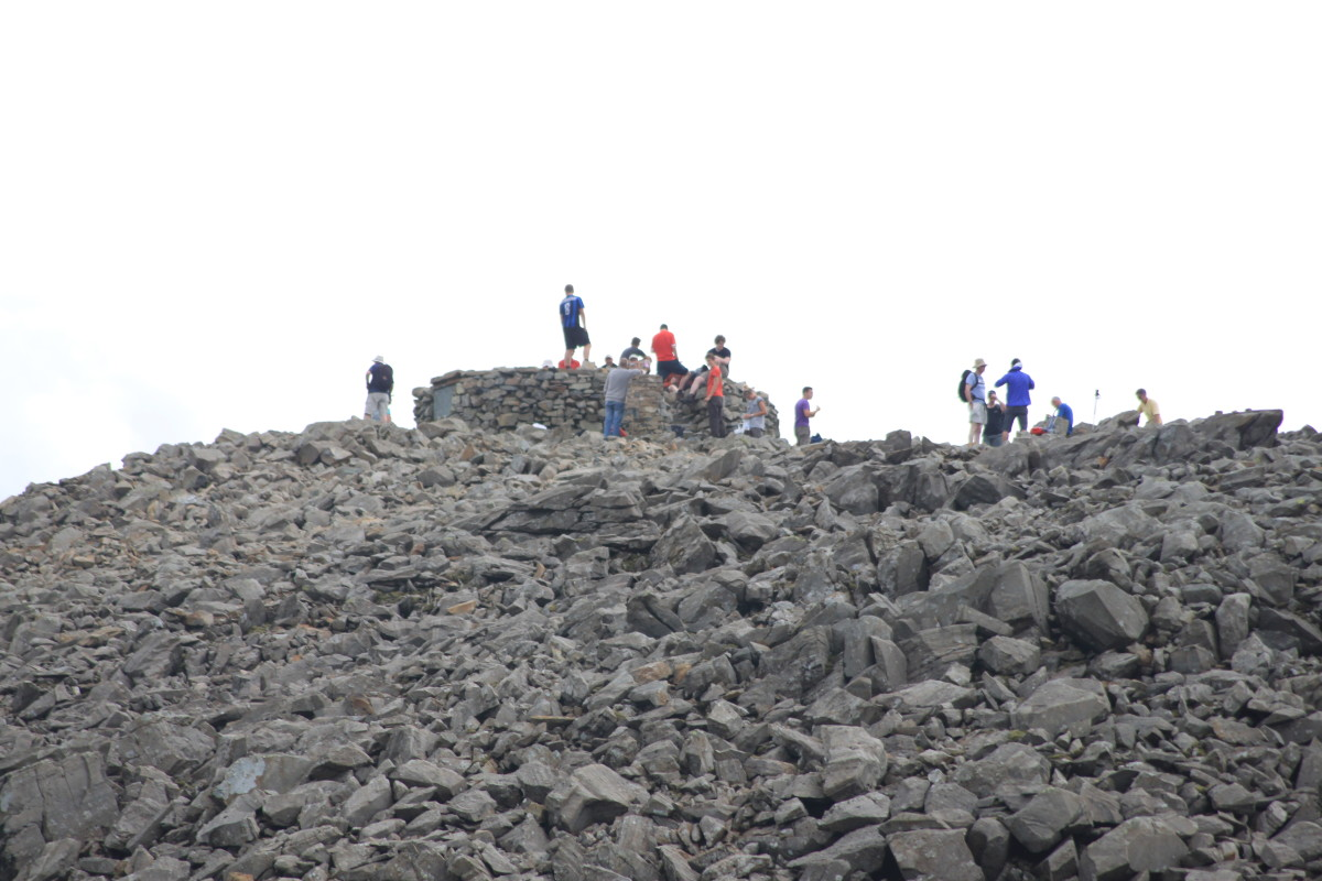 Groups of walkers on the Scafell Pike peak in jubilation