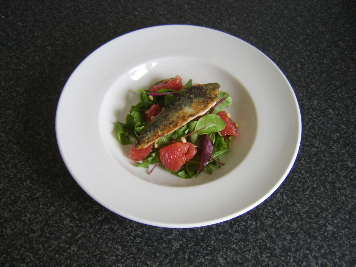 Mackerel fillet is laid on the salad bed and is ready to be garnished and served