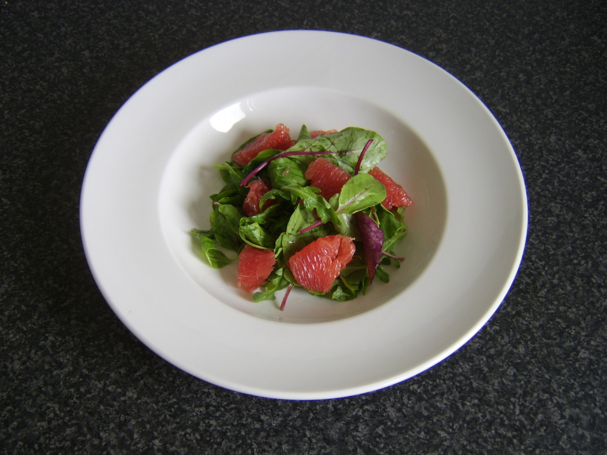 Salad leaves and red grapefruit segments are combined and laid as a salad bed in the serving plate