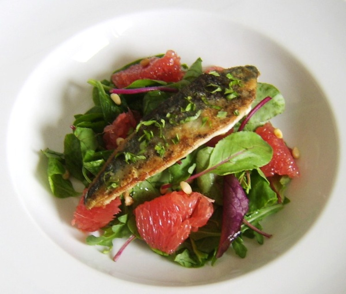 A simply and quickly pan fried mackerel fillet is served on a bed of mixed green salad leaves, red grapefruit and toasted pine nuts