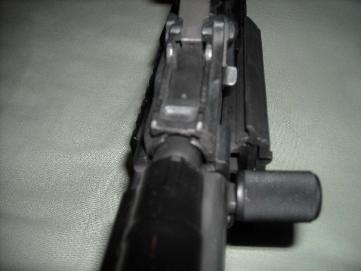Fold the rear sight forward and seat the front end of the dust cover into the notched area below the rear sight. While applying forward pressure to the notched area, push down firmly on the rear of the dust cover to properly lock into place the dust