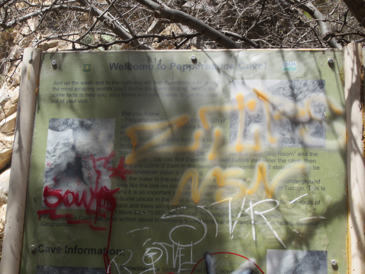 Graffiti covered sign at entrance to Peppersauce Cave in Santa Catalina Mountains near Tucson, AZ