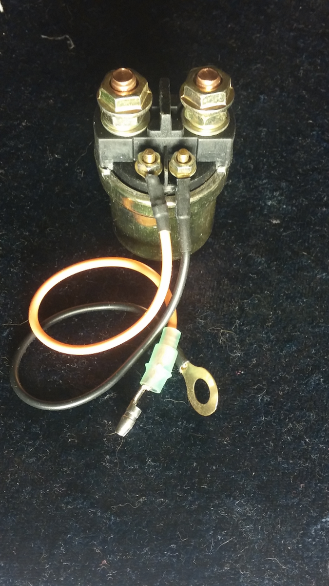 9.  The starter solenoid with four wire connections.