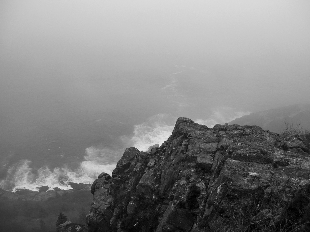 A section of Newfoundland's rugged coastline shrouded in fog. Waves pound the rocky shore far below.