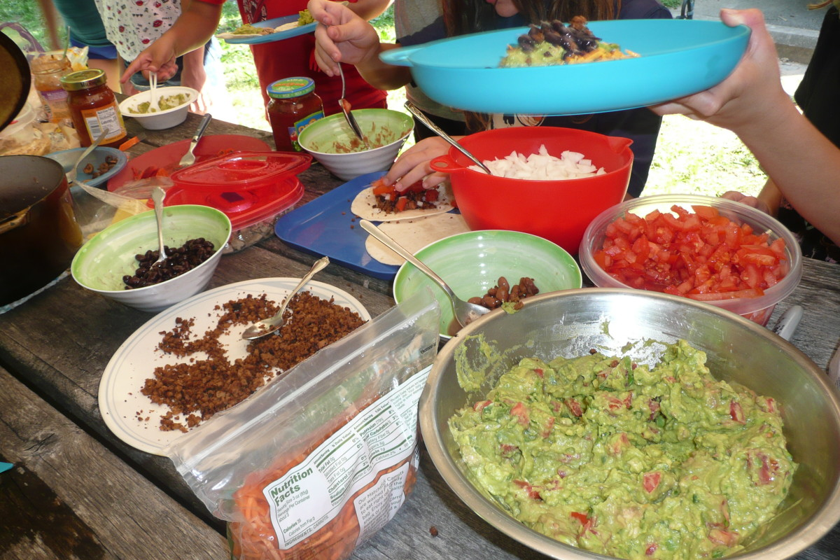 Campers enjoying tacos and wraps. Everyone has their own reusable mess kit, and food is served in reusable containers with reusable utensils.
