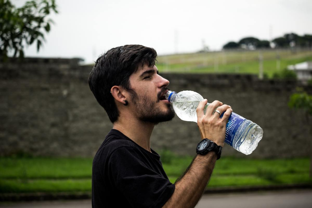 Man drinks water from a bottle.