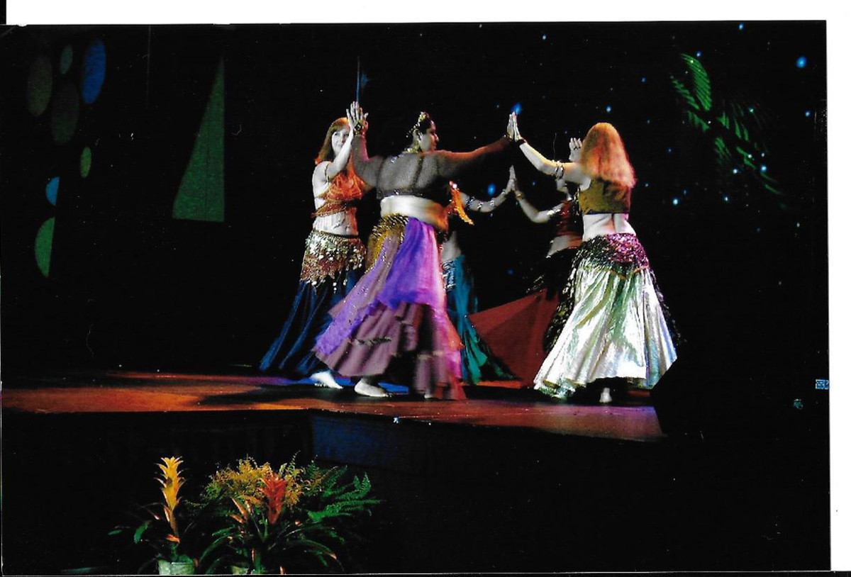 Belly dancers are having fun performing before an audience while continuing their aerobic exercises.