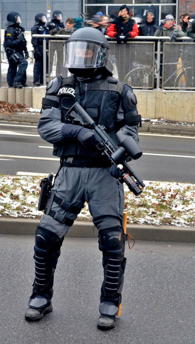 Policeman carries a pepper spray rifle