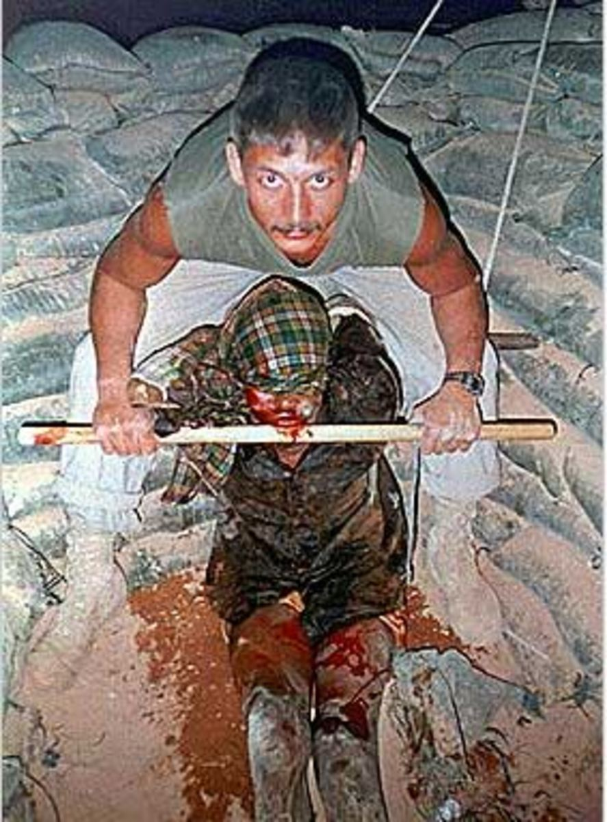 A Canadian soldier poses with his torture victim.