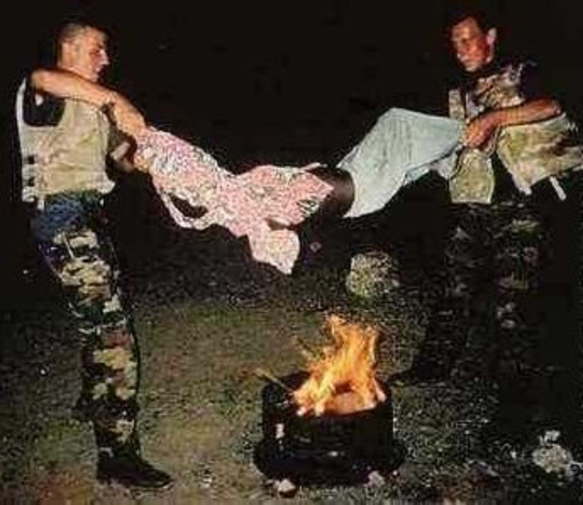 Two Belgian soldiers torture a Somali youth over an open fire