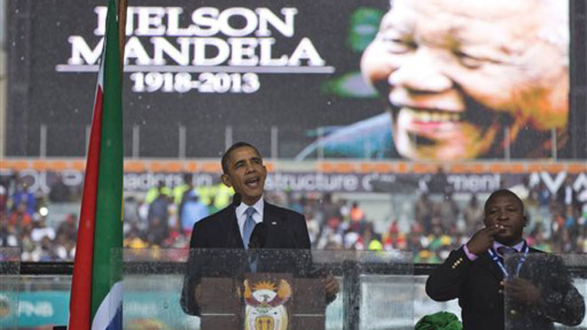 Fake Signifier and Signaler: President Barack Obama waves standing next to the sign language interpreter after making his speech at the memorial service for former South African president Nelson Mandela at the FNB Stadium in Soweto near Johannesburg,