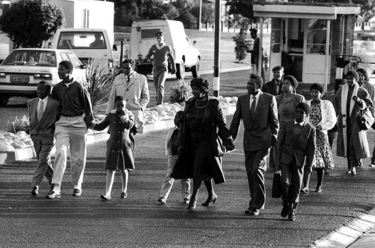Winnie Madikizela-Mandela, center, holding the hand of her son, the late Makgatho Mandela, and family walk out of Victor Verster Prison after visiting her husband Nelson Mandela. Mandela spent the last three of his 27 years behind bars at Victor Vers