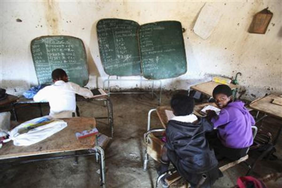 Children write notes from a makeshift blackboard at a school in Mwezeni village in South Africa's Eastern Cape Province in this picture taken June 5, 2012.