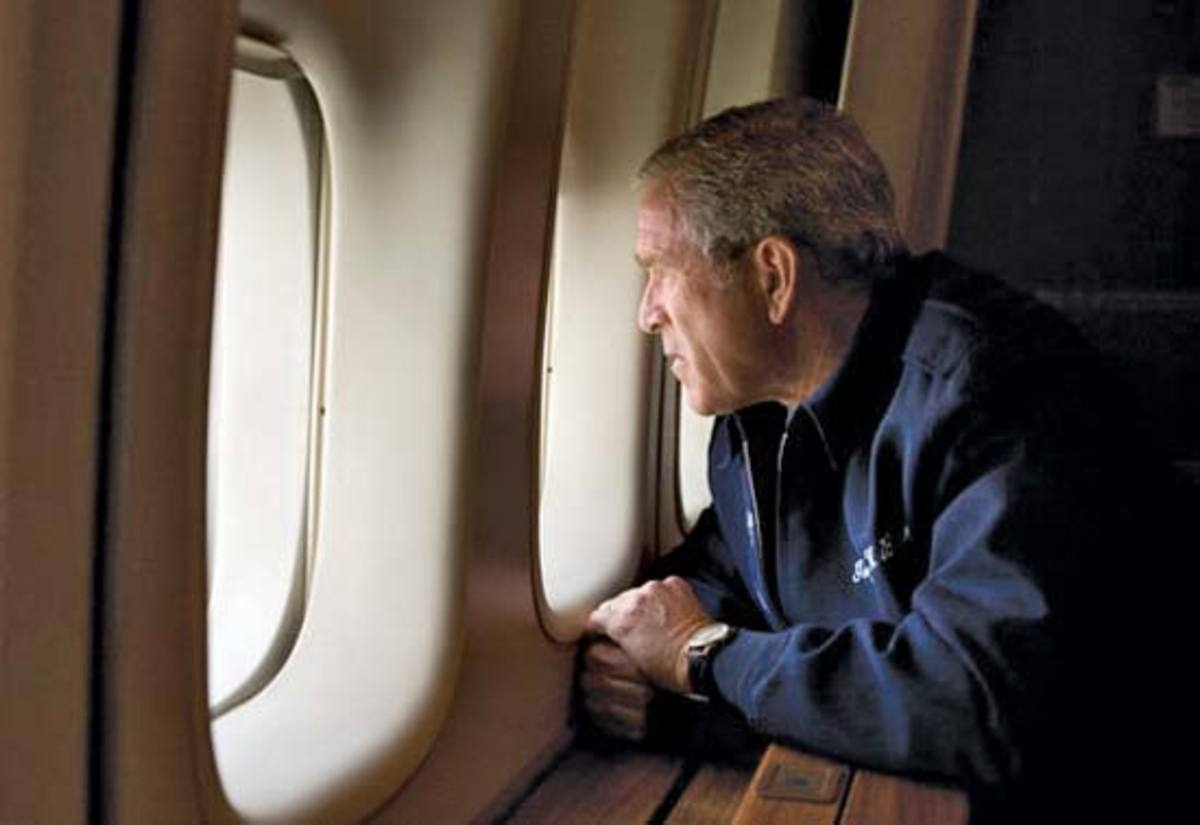 President Bush looking out the window of Air Force One observing the devastation of hurricane Katrina.