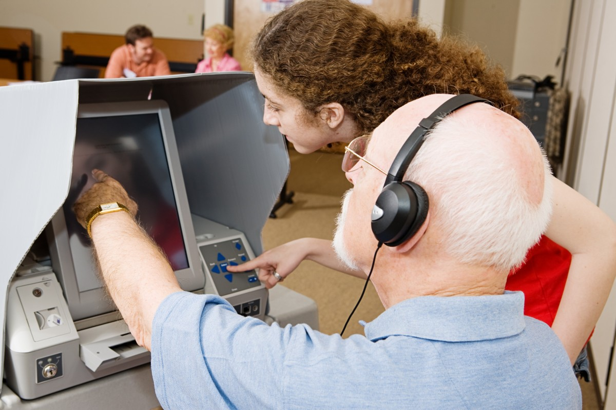 A poll worker shows a voter how to use an accessible voting machine.  Image © Can Stock Photo Inc. / lisafx.