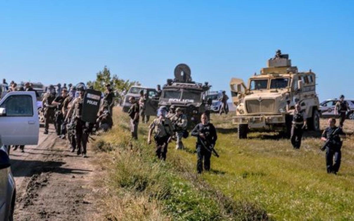 Militarized police facing protesters at Standing Rock Indian Reservation.