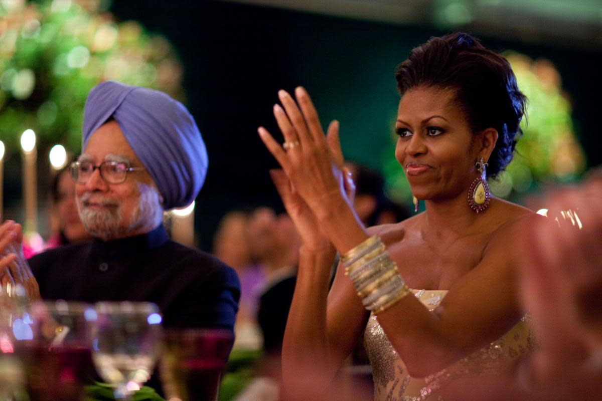First Lady Michelle Obama claps during the entertainment portion of the State Dinner for Prime Minister Manmohan Singh of India, held in a tent on the South Lawn of the White House, November 24, 2009.