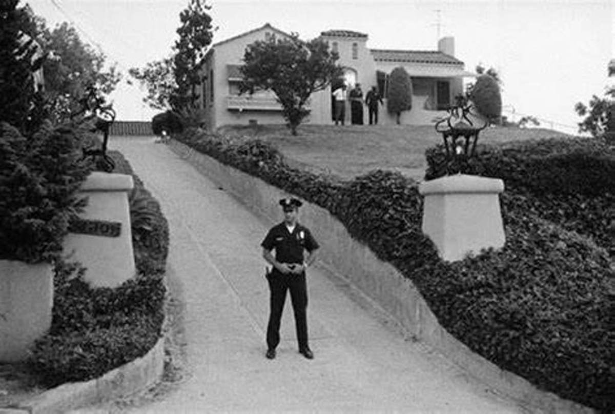 An officer stands guard in the driveway.