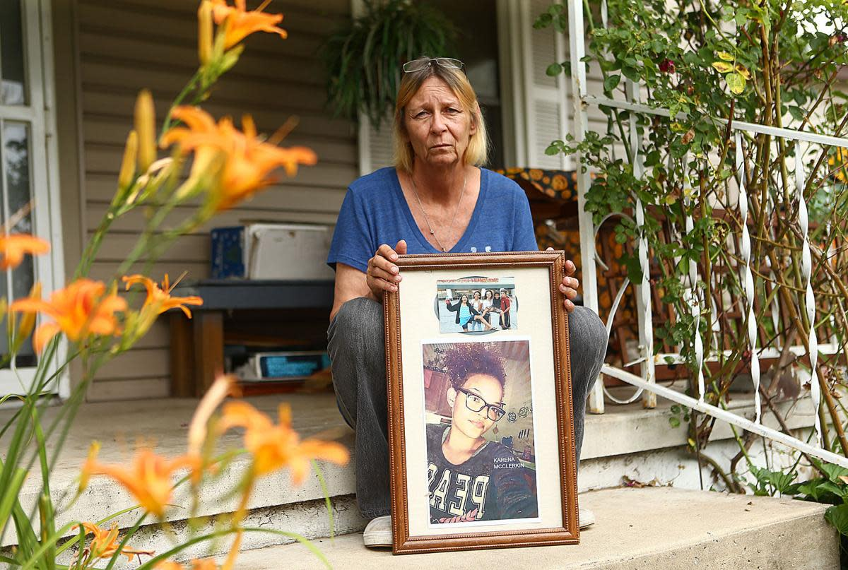 Karena's grandmother Gerry McClerkin, holding her picture on the front stoop of her home.