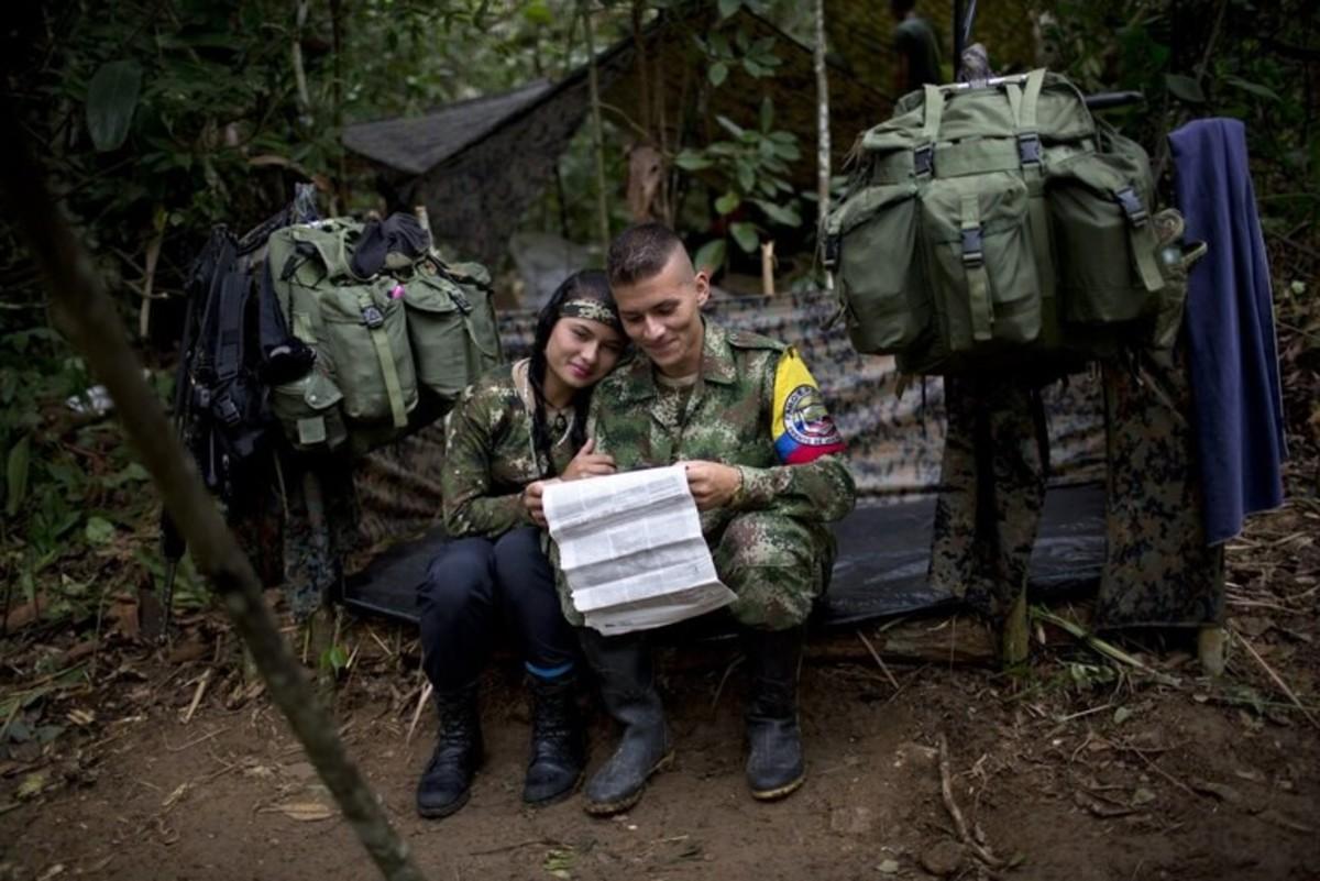 Juliana, sits alongside her boyfriend Alexis, in their tent.