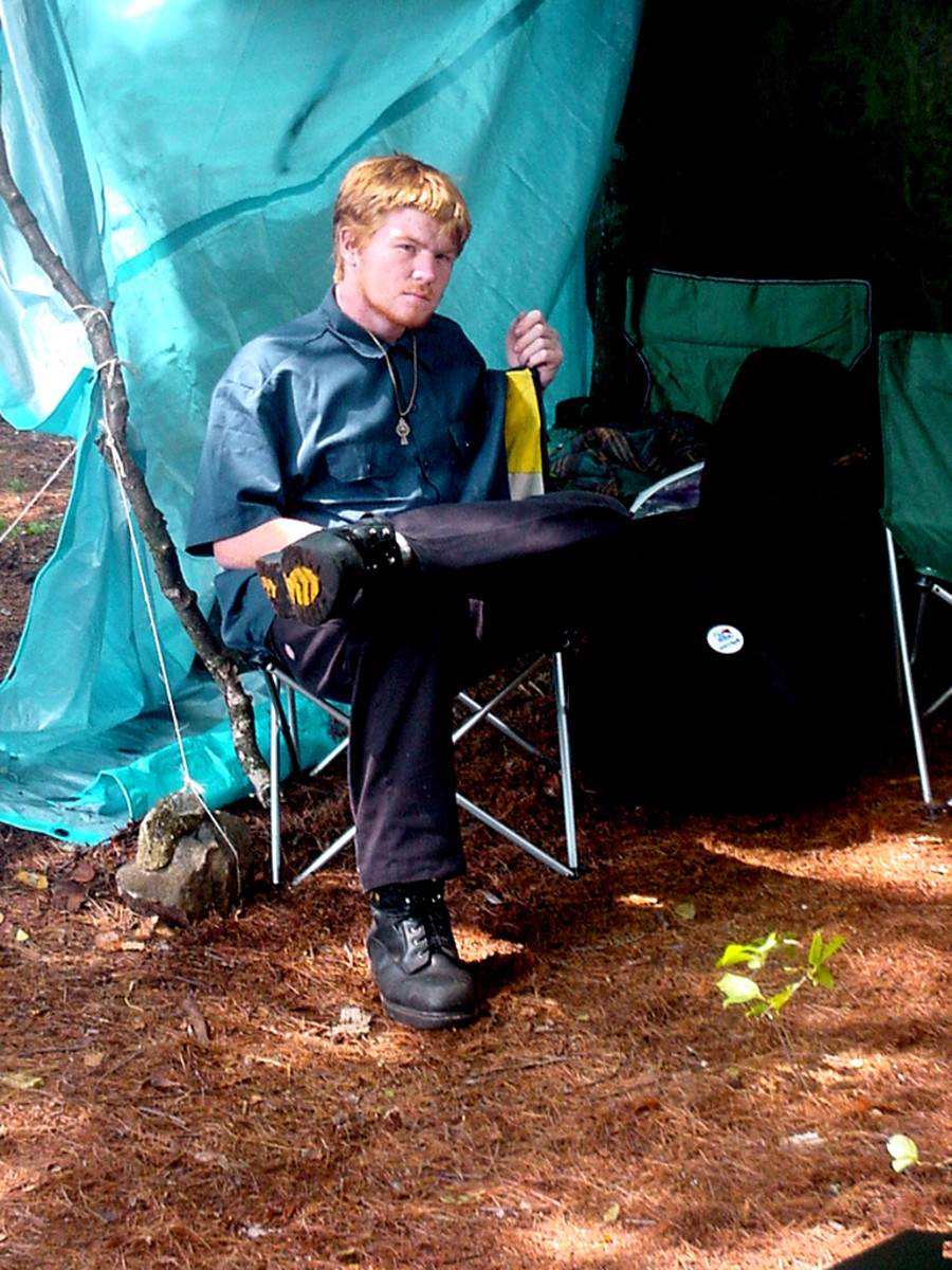 Young man in front of a tarp while camping. If it rains, you need covered space for eating or just hanging out.(Sorry to interrupt your reading, son)