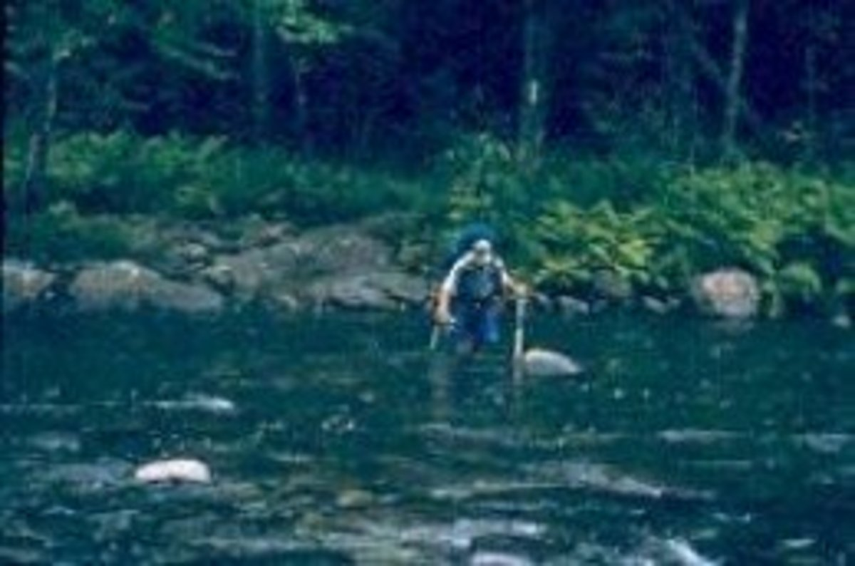 An A.T. hiker uses his trekking poles for balance while fording a river
