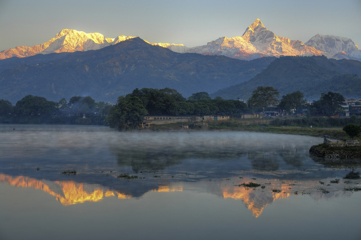 A view of Annapurna (left) and Machapuchare (right) and their reflection in  Phewa Lake from Pokhara.