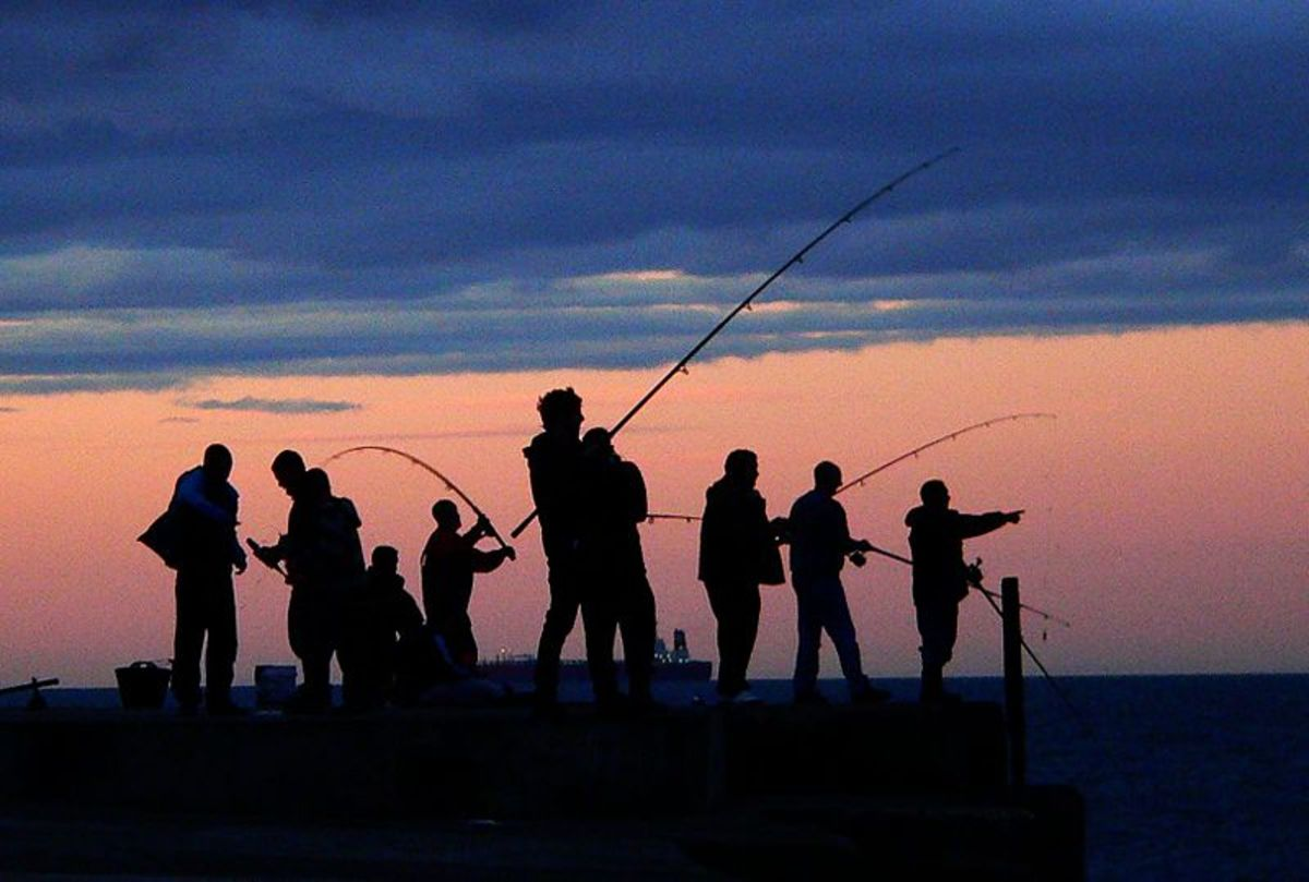 Fishermen enjoy an evening's fishing at South Gare breakwater, Redcar, England.