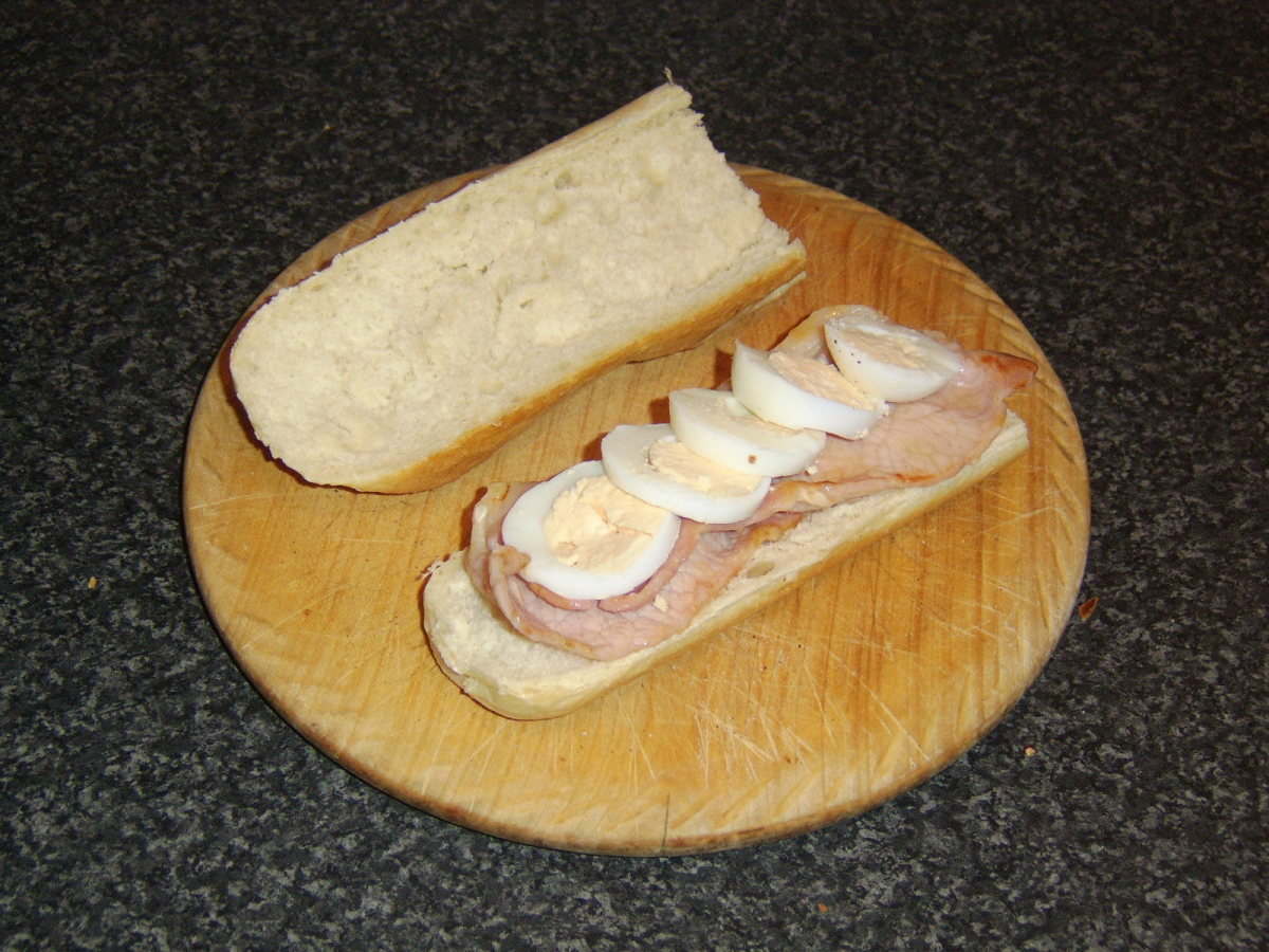 The bacon is added to the bread first, followed by the sliced egg.