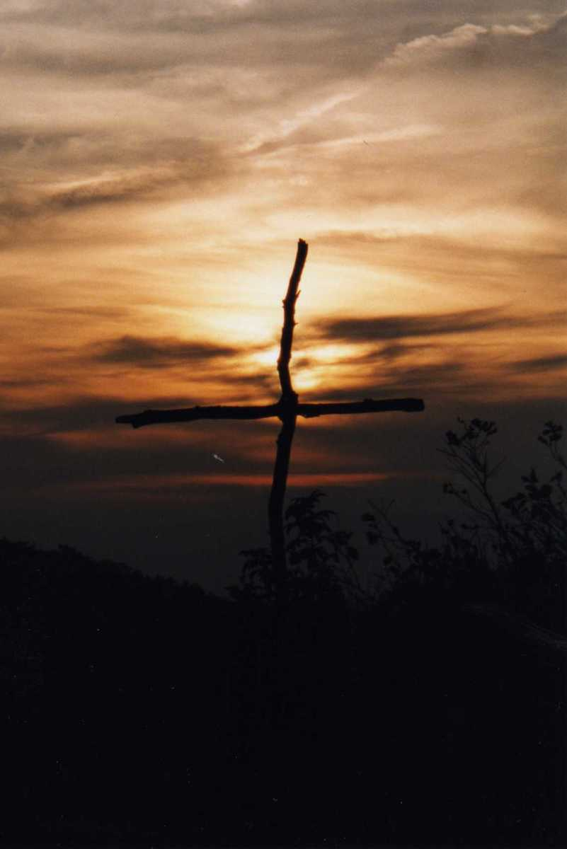 Sunrise behind a simple cross someone erected on a Virginia mountain top.