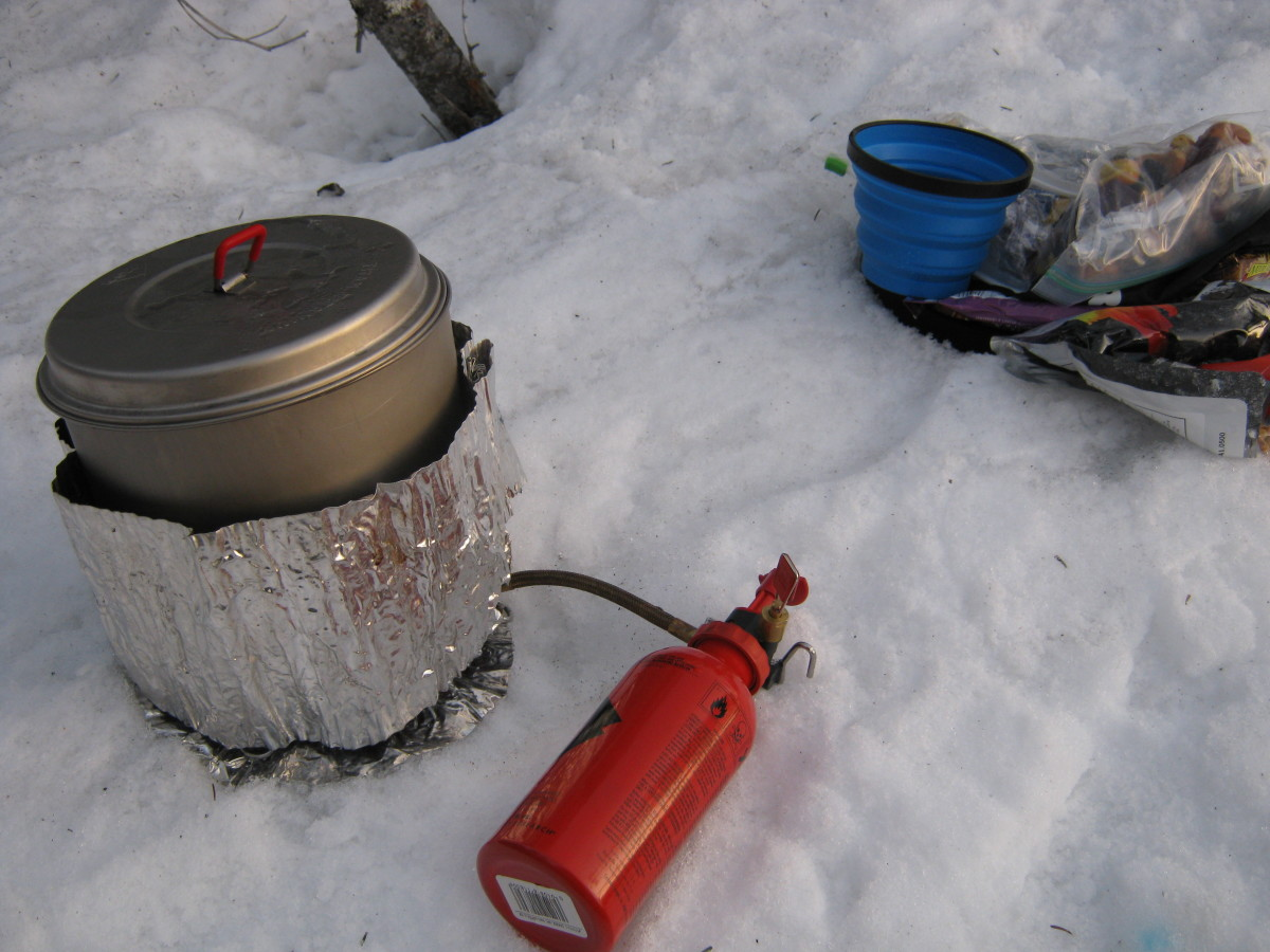 Melting snow using the MSR dragonfly on a winter backpacking trip.  The blue sea to summit cup is used for dipping boiling water into water bottles.